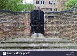 Black Metal Gate Door At Brick Fence Stock Photo Alamy
