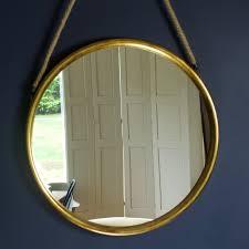 large round gold mirror on hanging rope