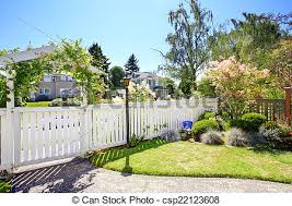 Front Yard With White Fence And Landscape Front Yard Landscape With Blooming Tree Decorative Bushes And White Wooden Fence