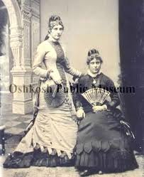 Full view studio shot of Ada Carter and Jennie Rudd Foot. Both of the women  are holding fans, Jennie Rudd, seated, is wearing a dark dress with a  locket. Ada Carter, standing,