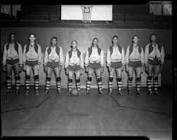 """Group portrait of Renaissance """"Rens"""" basketball team members, Tarzan  Cooper, John Isaacs, Eyre Saitch, """"Fats"""" Jenkins, Zack Clayton, Puggy Bell,  """"Pop"""" Gates, and """"Wee Willie"""" Smith, in gymnasium with basketball hoop in"""
