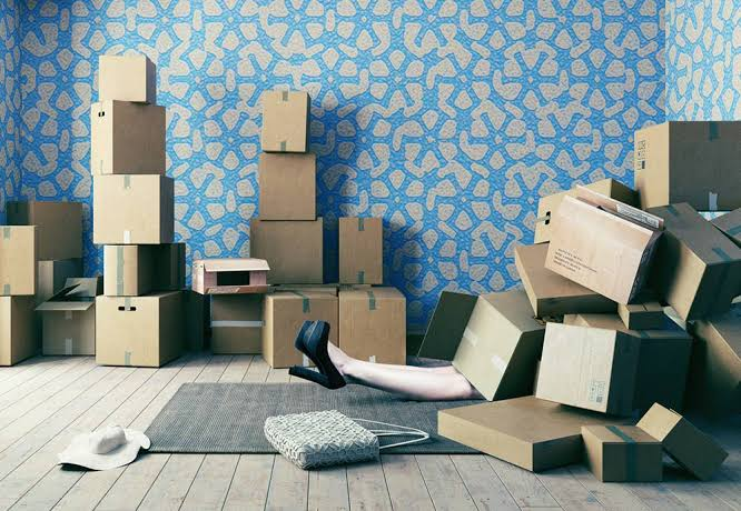Woman under pile of boxes as an inventory management challenge