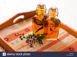 bottles with vinegar and oil on wooden tray inlaid with herbal ...