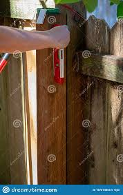 Woman S Hand Holding Small Level To Check Fence Post In Back Yard Stock Photo Image Of Building Level 167014854