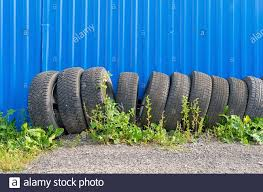 Sets Of Car Tires With Disks Are On The Street On The Ground Near The Fence Of The Cottage Stock Photo Alamy