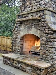 an outdoor stacked stone fireplace