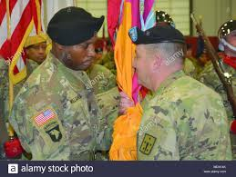 Command Sgt. Maj. Perry C. Williamson accepts the colors of the 59th  Ordnance Brigade from Col.