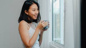 Happy beautiful asian woman smiling and drinking a cup of coffee ...