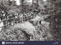 Group Of People Looking Down Pit Across The Fence Stock Photo Alamy