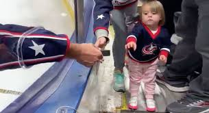 Hi, here's a baby Blue Jackets fan getting a puck from Adam Clendening