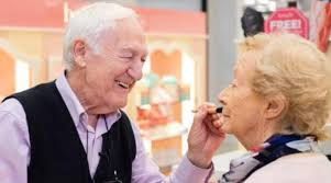 old man applies makeup for wife when