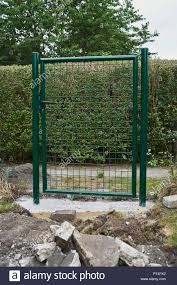 Garden Construction Installing A New Green Metal Entrance Gate And Fence Around The Perimeter For Safety And Security With Earthworks In The Foregroun Stock Photo Alamy