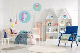Colorful Kids Bedroom Interior With A Unicorn And Ice Cream Poster Bed With Sheets Rabbit Pillow Shelves And Blue Armchair With A Blanket Stock Photo Download Image Now Istock