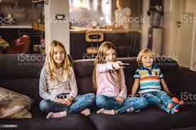 Happy Kids Watching Tv On Sofa In The Living Room Stock Photo Download Image Now Istock