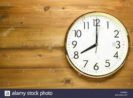 wall clock on the wooden wall at time 8am or 8pm Stock Photo - Alamy