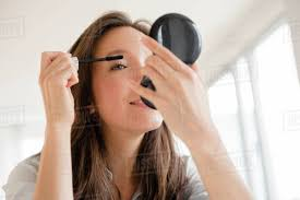 woman applying makeup in pact mirror
