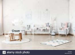 Pink Blanket On Grey Armchair In Pastel Kid S Room With Small Table And Plush Toy On White Cabinet Stock Photo Alamy