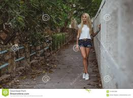 Beautiful Blonde In A White T Shirt And Short Denim Shorts Standing At The White Picket Fence In An Urban Alley Women S Stock Photo Image Of Background Long 101562280