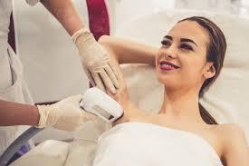 Mulher está sorrindo enquanto médico está fazendo a depilação a ...