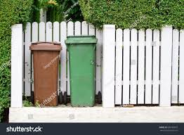 Garbage Cans Near Fence Miscellaneous Stock Image 696183019