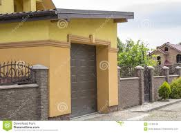 View From The Clean Paved Street Of Detached Garage With Big Automatic Door New Residential Cottage With Balcony Behind Brown Br Stock Photo Image Of Credit Interest 121320126