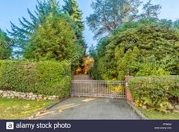 Fence Of Bushes And Stones Metal Retractable Gates Street Lights On Brick Poles Green Trees And Blue Sky Stock Photo Alamy