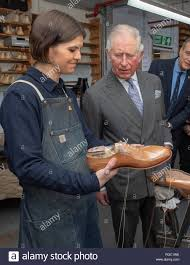 Adele Williamson shows the Prince of Wales, some shoes she is making,  during his visit to Tricker's Ltd in Northampton where he toured the  shoemaker's factory in its 190th year Stock Photo -