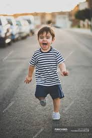 portrait of cute boy in shorts running