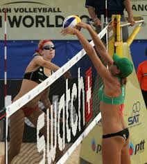 USA's Summer Ross smashes the Mikasa as USA's Jennifer Fopma blocks