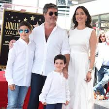 Simon Cowell with Lauren Silverman, Eric and Adam receiving his ...