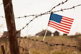 American Flag On Old Barbed Wire Fence Blurred Buildings In Stock Photo Picture And Royalty Free Image Image 121815183