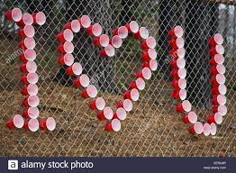 Using Red And White Plastic Cups On A Chain Link Fence To Spell I Stock Photo Alamy