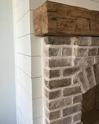 whitewashed brick rustic wood mantel