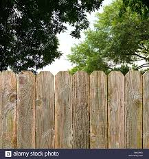 Rustic Wood Fence Provides Backyard Privacy And Security With Green Shade Trees In The Background Stock Photo Alamy