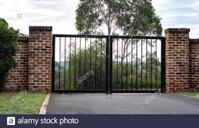 Black Metal Wrought Iron Driveway Property Entrance Gates Set In Brick Fence Lights Green Grass Garden Trees Stock Photo Alamy