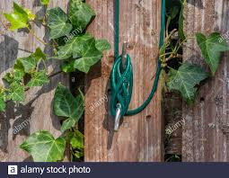 A Green Washing Line Tethered To A Wooden Fence With A Metal Hook Stock Photo Alamy