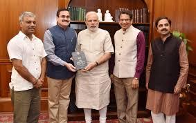 PM Narendra Modi presented with a copy of the book, 'The Modi ...