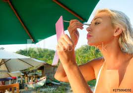blond woman holding mirror retouching