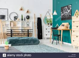 Black Chair At Wooden Desk In Kid S Room Interior With Green Mattress Near Patterned Carpet Stock Photo Alamy