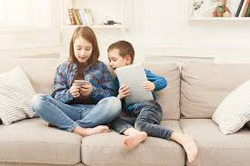 Two Kids With Gadgets On Couch At Home Stock Photo Download Image Now Istock
