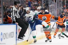 Iiro Pakarinen of the Edmonton Oilers hits Brandon Sutter of the ...