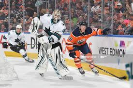Aaron Dell of the San Jose Sharks plays the puck as Tyler Benson ...