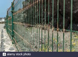 Wire Mesh Fence Closeup Photo Green Bush And Huge Cave In Blurred Background Thin Pillars Decorative Board Front Of Garden Building Construction Stock Photo Alamy