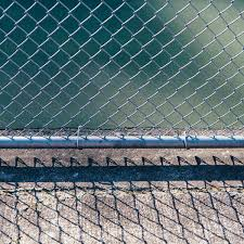 Close Of Up Chain Link Fence Basketball Court In Background By Rialto Images Fence Fencing Stocksy United
