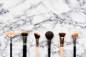 makeup brushes on white marble