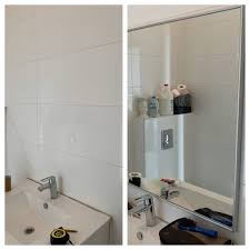 hanging a mirror on the tile bathroom