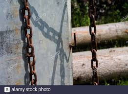 An Old Rusty Chain In Front Of A Steel Plate In The Background You Can Also See Tree Trunks And Shrubs Stock Photo Alamy