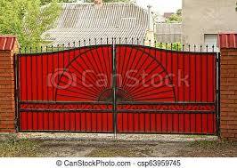 Large Red Metal Gates On A Brick Fence In The Street Large Red Closed Metal Gates On A Brick Fence In The Street