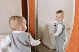 El bebé de diez meses se para frente al espejo y juega consigo ...