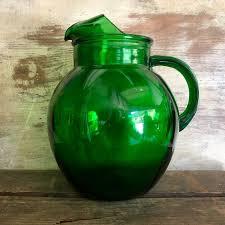 green glass pitcher bir in a barn